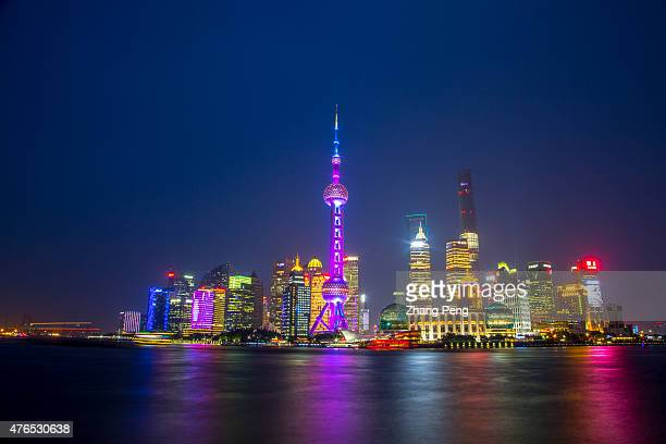 Colorful neon lights of Oriental pearl tower and skyscrapers in Pudong are reflected on Huangpu river at night Oriental pearl tower is the landmark...