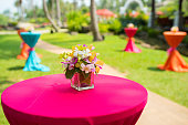 Colorful orchid in glass jar on bar desk with vivid desk cover decorated in lawn,India wedding decoration.