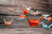 Colorful many origami paper cranes on wooden background