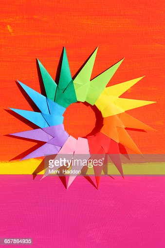 colorful origami starburst on painted backdrop stock photo