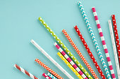 Colorful paper drinking straws on blue background. Flat lay with copy space.