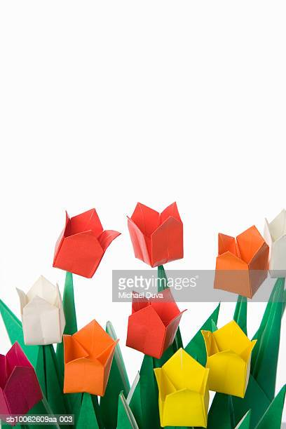 Colorful paper tulips against white background, close-up