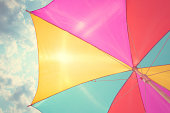 Colorful parasol in blue sky with clouds