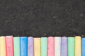 Colorful pastel sidewalk chalk on dark asphalt background. Top view