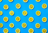 Colorful fruit pattern of fresh lemon slices on blue background. From top view