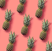Colorful fruit pattern of fresh pineapples on pink background. From top view