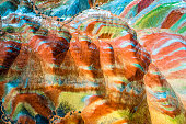 Colorful Rainbow Mountains in Zhangye National Geopark; aerial top down view on sandstone hills and mountain chains covered with amazing pattern due to deposition of minerals, Gangsu, China, May 2017