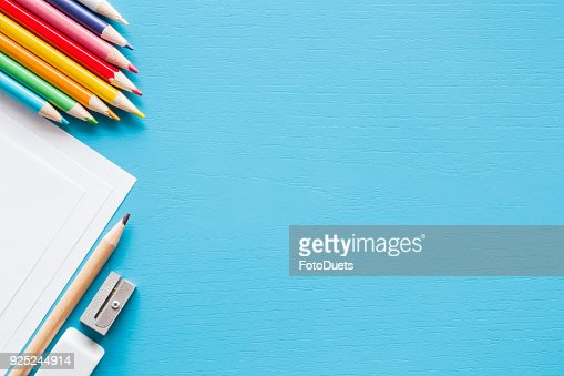 Colorful pencils, white papers and metal pencil sharpener. Empty place for text or drawing on the blue background. Childhood creative art concept. Flat lay. : Stock Photo