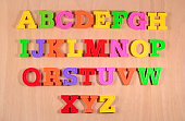 Colorful plastic alphabet letters on a wooden background