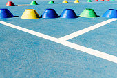 Colorful plastic cones on a blue cement tennis court with white lines background.