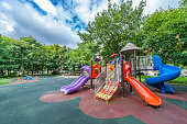 Colorful playground equipment for children in public park in summer