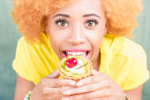 Portrait of a pretty african woman in yellow t-shirt holding a sweet dessert with cherry on the green background