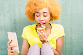 Portrait of a pretty african woman in yellow t-shirt making selfie photo with sweet dessert on the green background