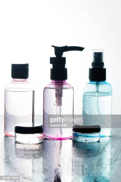 colorful Realistic cosmetic bottle on wet and darken background. Cosmetic package collection for cream,