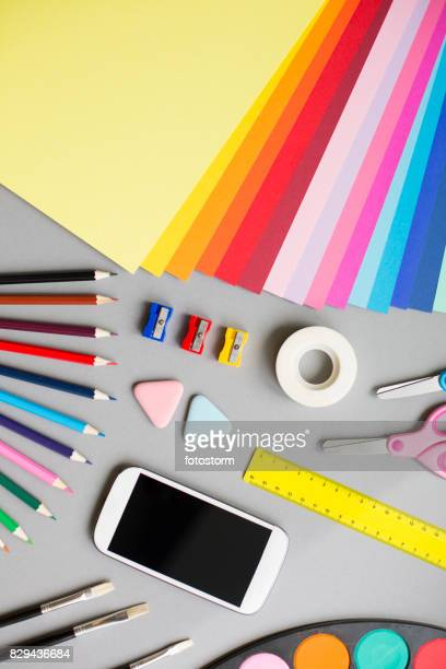 Colorful school supplies on grey background