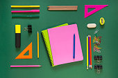 Colorful school supplies, pink book on green background. Top view, flat lay, copy space.