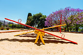 Colorful seesaw viewed from the side in the sandbox of a park