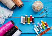 Sewing and knitting items, threads, cloths, measuring tape and scissors, colorful and organized
