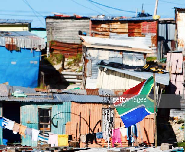 Colorful shacks with washing line and South African flag