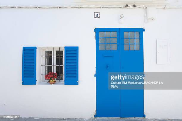 Colorful shutters and flowers on house