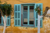 Colorful shutters of old colonial house now used as a school on Goree Island in the Atlantic Ocean outside of Dakar in Senegal West Africa