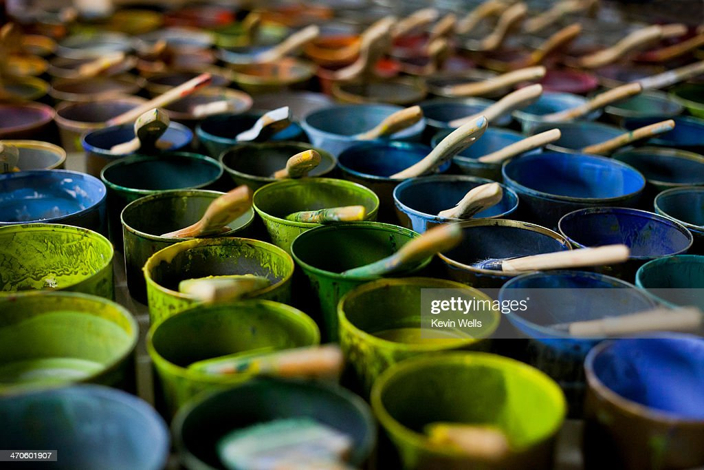 Colorful, small cans of paint with brushes in them : Stock Photo