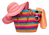 Colorful striped beach bag with a straw hat towel and sunglasses, isolated on white