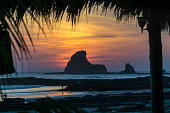 Colorful sunset on the beach in Nicaragua with a rock in the front
