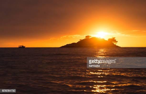 Coloré coucher de soleil sur l'océan avec une vue sur une petite île