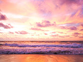 Colorful sunset on the tropical beach with beautiful sky, clouds, soft waves