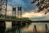 Beautiful sunset featuring dense clouds over the Interstate Bridge. A drawbridge spanning the Columbia River.  Portland, Oregon and Hayden Island is to the south as viewed from the Washington State si