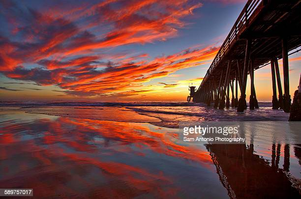 Colorful Sunset with Reflections at Beach Pier