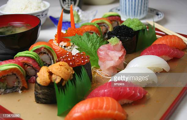 A colorful sushi tray on a wooden board