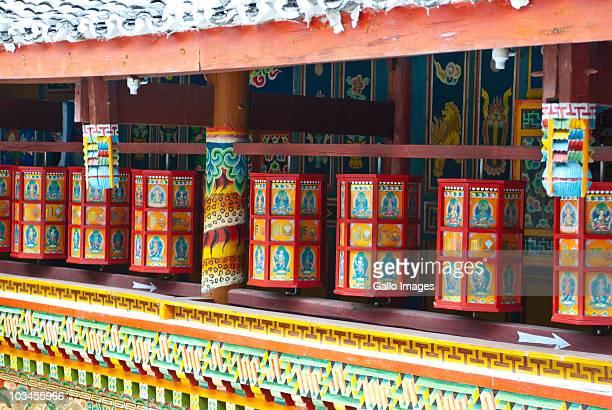 Colorful Tibetan painting on courtyard walls and prayer wheels at Zechawa Village house, Jiuzhaigou National Scenic Area, Sichuan Province, China