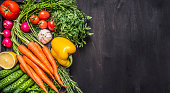 Colorful various organic farm vegetables carrots cherry tomatoes, garlic, cucumber, lemon, pepper, radish, wooden spoon salt pepper colored, oil wooden rustic background top view  border, place text