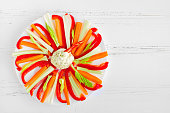 Colorful vegetable sticks with dip sauce in a plate on white wooden table with place for text. Healthy appetizer crudites - cut fresh red pepper, carrot and celery. Copy space. Top view.