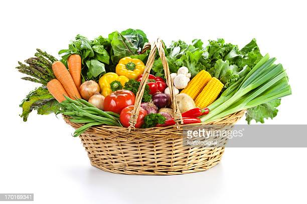 Colorful vegetables in wicker basket isolated on white backdrop