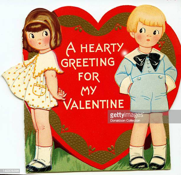 A colorful vintage cartoon greeting card depicts a a boy and a girl with a heart between them that reads 'A hearty greeting for my Valentine'