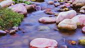 Small water stream running among beautiful colored rocks.