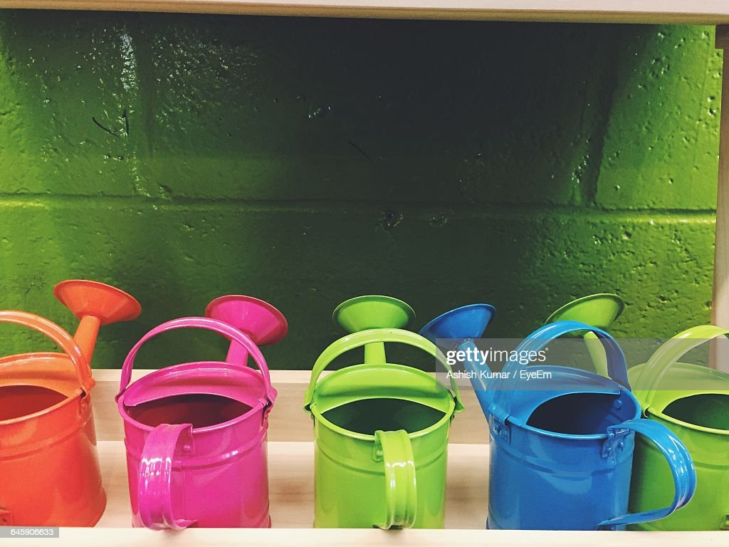 Colorful Watering Cans Against The Wall
