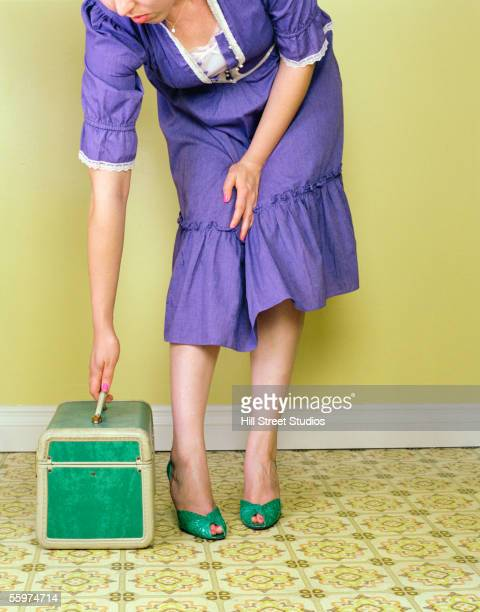 Colorful woman reaching for vintage suitcase