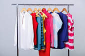 colorful womens clothes on wood hangers on rack on gray background. women's closet