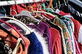 rack of fast fashion colorful women's sweaters on display for reselling,recycling,donation,reusing or welfare for second life sold at flea market, outdoors