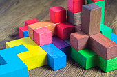 Abstract construction from wooden blocks tetris shapes. The concept of logical thinking, geometric shapes. Colorful wooden building blocks.