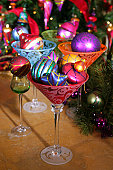 Colorfully decorated Christmas tree baubles arranged in cocktail glasses
