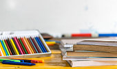 School and studying concept and idea, books, pencils and pens on top of wooden table