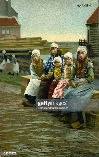 Colorized postcard features a portrait of a group of Dutch girls in traditional costume as they sits on bend Marken Holland 1915