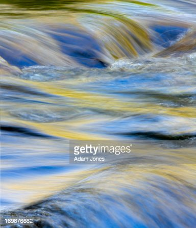 Colors reflected on flowing mountain stream