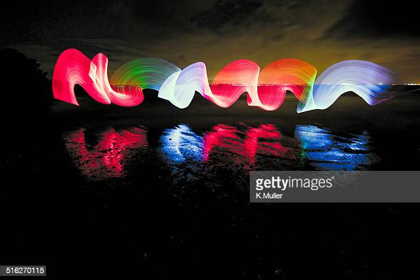 Coloured light painting at beach with reflections
