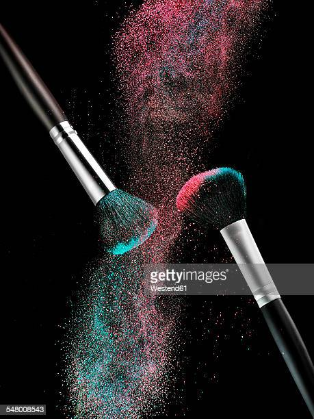 Coloured make-up powder and two beauty brushes in front of black background